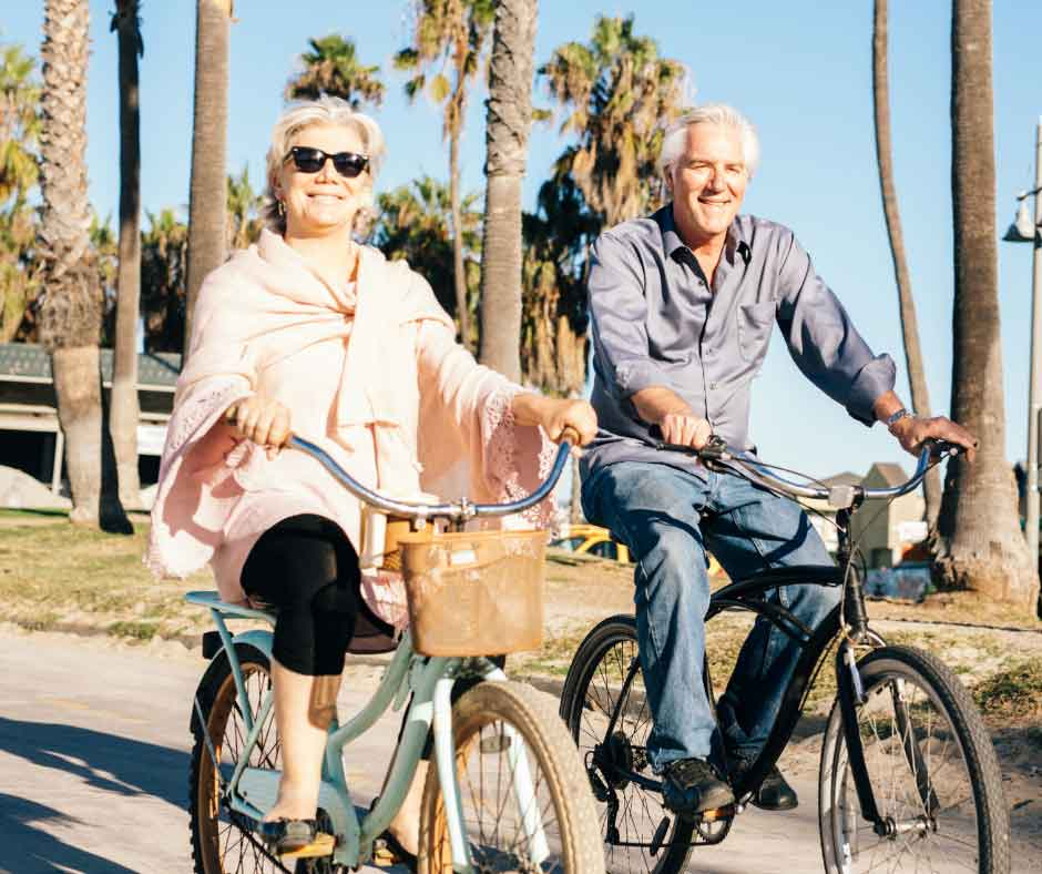 Active senior couple on bike, planning for healthcare costs in retirement blog